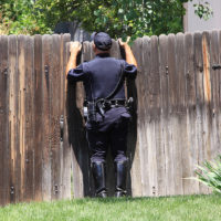 illegal search concept - policeman looking over fence