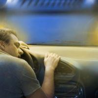 Guy alseep behind the wheel