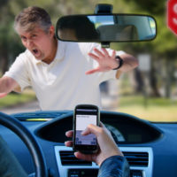 Distracted driver texting with phone is about to hit a pedestrian