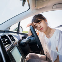 young female driver sleeping behind wheel as part of drowsy driving concept