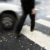 Pedestrian walking on street almost gets hit by car