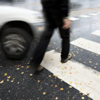 Pedestrian accident about to happen with blurry focus on car and crossing man