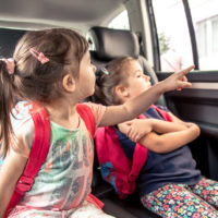 Two children riding in car back seat