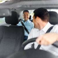 middle aged male passenger talking to car driver