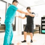 Physiotherapist Helping Athlete To Walk Between Cones In Hospital