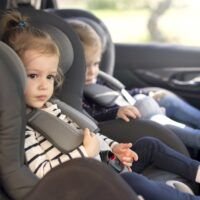 cute small twins in car seats in the car