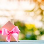 Home model tied with pink ribbon on bokeh in the public park, The buy new house or real estate as gift to family or the one loved concept.