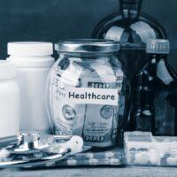 Saving money for health care insurance - money glass, stethoscope, pills and bottles